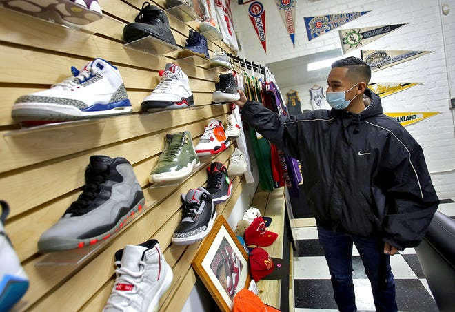 Eric Ortega arranges shoes at Retroville located at 214 N. Lafayette St. in Shelby on Tuesday.