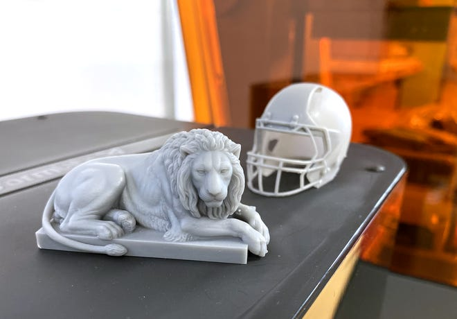 A lion figurine and football helmet that were printed using the Formlabs Form 3 resin printer.