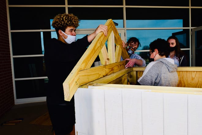 From left to right,Shawnee Middle School eighth graders Jordan McClain, Miller-DeBoer, Orlin McConnell-Abell andAehrellTimmbuild a playhouse.