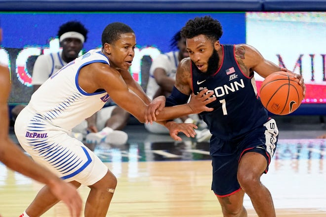 Connecticut's R.J. Cole (1) drives against DePaul's Charlie Moore Monday, Jan. 11, 2021, in Chicago.
