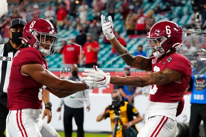Alabama wide receiver John Metchie III, left, congratulates wide receiver DeVonta Smith on his touchdown against Ohio State during the College Football Playoff national championship game, Monday, Jan. 11, 2021, in Miami Gardens, Fla.