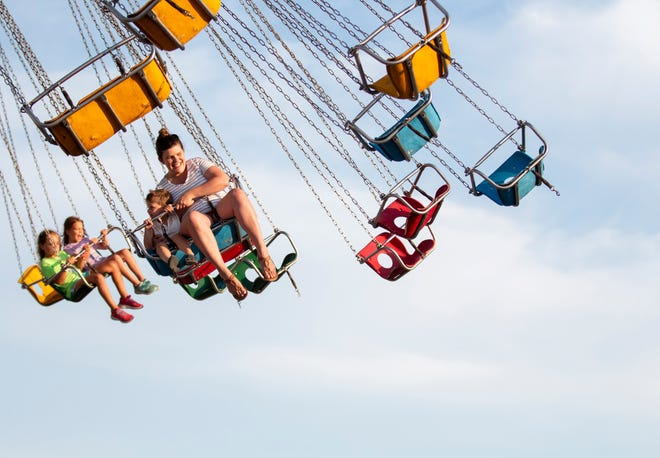 People have fun on the swing ride at Carolina Beach Boardwalk's amusement park Thursday, July 25, 2019 in Carolina Beach, N.C. The town council will vote to bring the amusement rides back to the boardwalk in February.