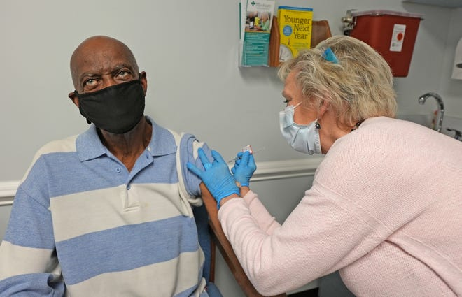 Earl Coburn receives a COVID-19 vaccine from Deborah Musselwhite, RN, with NHRMC Physician Group - New Hanover Medical Group. The Physician Group is offering vaccine appointments to eligible primary care patients in accordance with the state's vaccine distribution plan.