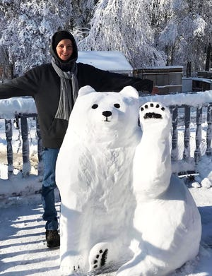 Middleoboro artist Dawn Gould with a polar bear snow sculpture on her back porch.