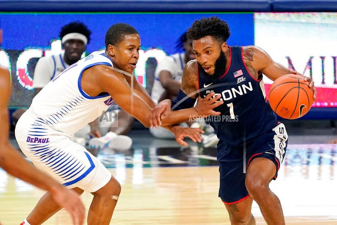Connecticut's R.J. Cole (1) drives against DePaul's Charlie Moore during the first half of an NCAA college basketball game Monday, Jan. 11, 2021, in Chicago.