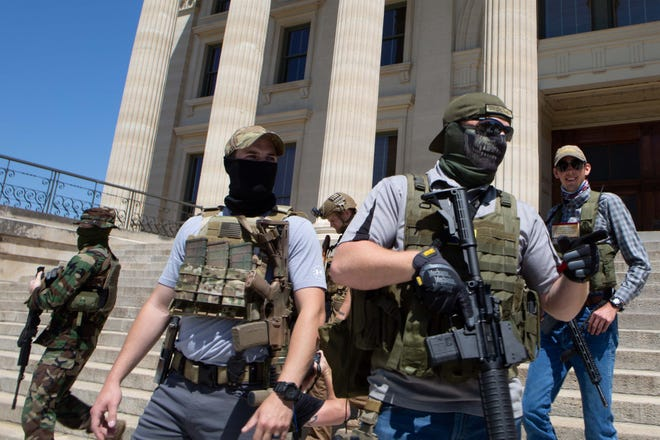 Protesters holding rifles and wearing vests walk down the steps at the Kansas Statehouse on April 23, 2020.