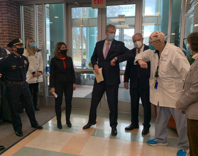 Gov. Charlie Baker, center, visits the Worcester Senior Center in January, and is greeted by City Medical Director Dr. Michael Hirsh.