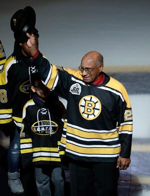 Former Boston Bruins' Willie O'Ree tips his hat as he is honored before a game in 2018. The Bruins will retire his jersey this season.