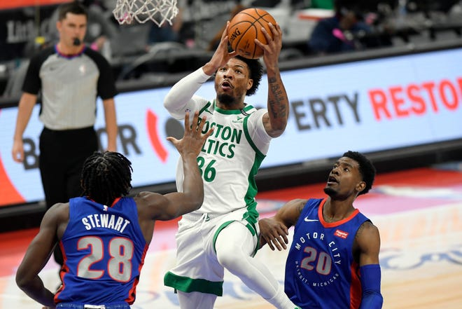 Boston's Marcus Smart, middle, drives in between Detroit's center Isaiah Stewart, left, and guard Josh Jackson during a game last week. The Celtics have had their last three games postponed due to coronavirus protocols.