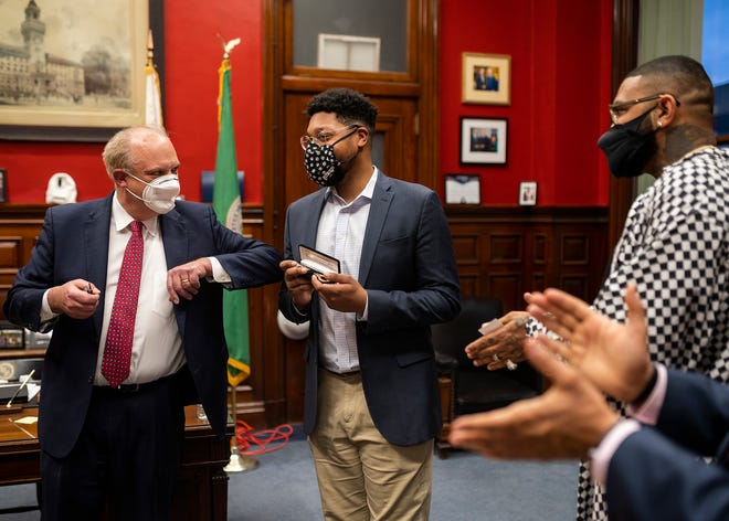 Mayor Joseph Petty presents Che Anderson, working his last day as deputy cultural development officer for the city, a key to the city along with rapper Joyner Lucas, a Worcester native, Tuesday at City Hall.