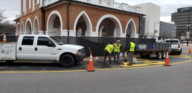 Workers begin removing the slogans 'Black Lives Do Matter' and 'End Racism Now' from around the Market House in Fayetteville on the morning of Jan. 11, 2020.