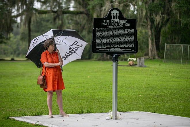 A visitor leaves flowers and reads a historical marker about the lynching of six Newberry residents in 1916.