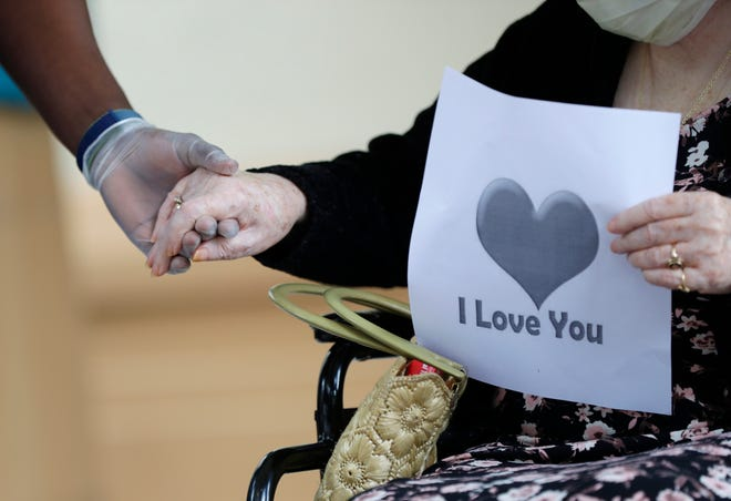 An 87-year-old woman holds the hand of a care coordinator in a one hand and a sign in another as her friend drives by for a visit on July 17, 2020, at a senior living facility in Miami.