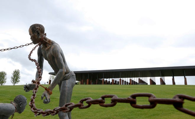 A statue of a chained man is shown at the National Memorial for Peace and Justice, which honors thousands of people killed in racist lynchings, in Montgomery, Ala.
