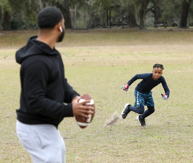 Jayden Harriot, 9, breaks out of his stance as he and his dad Aaron run some football drills at Squirrel Ridge Park in Gainesville Fla., Jan. 12, 2021.