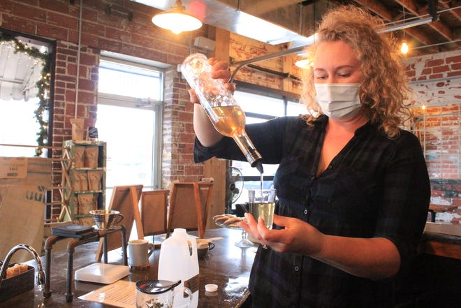 Fort Smith Coffee Co. owner Kaity Gould measures syrup for a half-gallon iced beverage on Wednesday, Jan. 6, 2021. Gould has marketed the coffee shop's half-gallon iced lattes on the shop's social media pages.