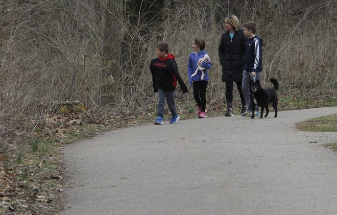 Annie Lovegrove (third from left) walks the Olentangy Trail with her children Dean, 6; Shay, 7; and Neil, 10; and their dog, Bear. The city of Columbus announced plans to close the gaps in the trail with two bridges.