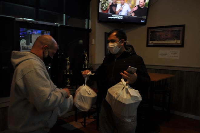 Hilliard resident Ghafar Khan, 30, a driver for Uber Eats, picks up an order Jan. 11 at Nasty's Sports Bar & Restaurant, 4561 Scioto Darby Road in Columbus, from owner Frank Profeta, just before kickoff of the NCAA football championship game between Ohio State University and the University of Alabama. Columbus has a 15% cap on commission fees for third-party food-delivery services. Some central Ohio cities, including Dublin and Hilliard, have considered capping the fees but have chosen not to do so.