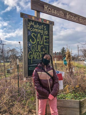 Ten-year-old Dyaunia Denny stands in front of the entrance of Kossuth Street Garden, a communal greenspace in the Southern Orchards neighborhood east of German Village. Dyaunia and other supports of the garden are trying to save the greenspace, which is being targeted for a housing development.