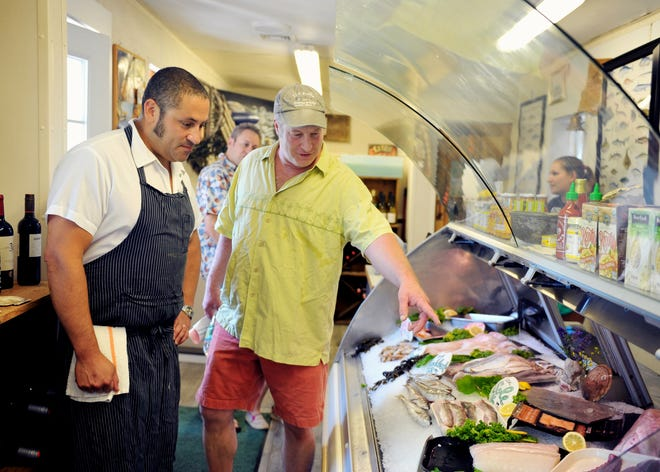 Joby Norton of Mullaney's Fish Market, right, with Robin King of Oro, points to a display of fresh seafood.  Mullaney's will use funds from the first round of SANDS grants to purchase a HEPA air purifier for their harborside fish market, eliminating airborne particles making it safer for customers and employees.