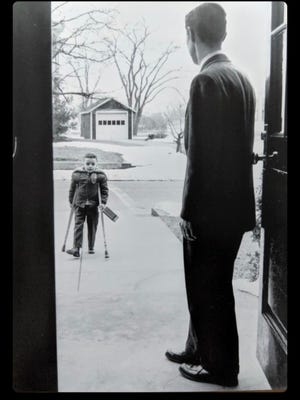 Eddie Randolph, who contracted polio in 1955, arrives at the Roland Green School in 1956 and is greeted by Principal Joseph LaLiberte. The photo taken by Mansfield News photographer Dick Yager is registered with the Library of Congress.