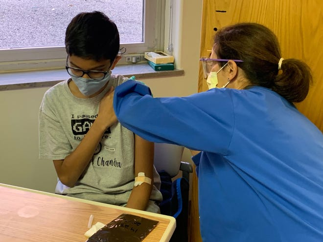 A 12-year-old boy receives a shot during a COVID-19 Pfizer vaccine trial in October at Cincinnati Children's Hospital Medical Center. This trial is for kids age 12-16. At some point, infectious disease expert pediatricians expect a trial for children younger than 12.