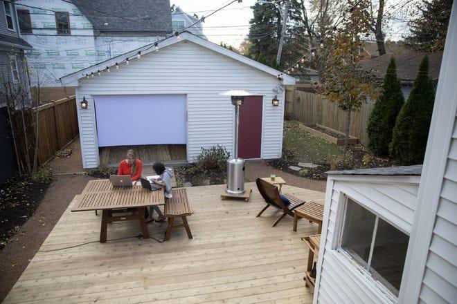 Amy Nedoss dan putrinya yang berusia 9 tahun, Jin, mengerjakan laptop mereka di halaman belakang yang baru direnovasi di Evanston, Illinois.