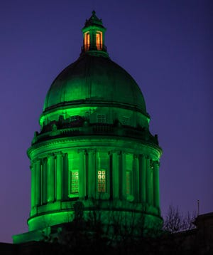 As dusk settles on early Monday, Jan. 11. evening, the capitol rotunda is lit green to honor those lost to Covid-19 as well as the American flag at half staff to honor Brian Sicknick, the Capitol Police Officer who was attacked and killed in DC by Trump supporters January 6.