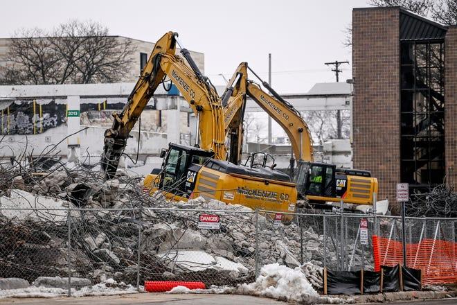 Excavators work to demolish the Gannon parking ramp on the Lansing Community College campus on Monday, Jan. 11, 2021, in Lansing.