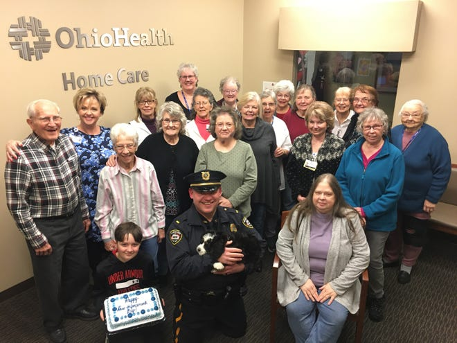 Hospice volunteers and others celebrating National Law Enforcement Day. Pictured are (back row, left to right): Joe Morman, Theresa Hunt, Diana Fry, Dawn Reidlinger, Linda Aufdencamp, Marilyn Andrews, Beth Lauer, Ethel Cook, Rosanna Becker, Norma Vanderboegh; (middle row): Bonnie Jolliff, Sandy Smith, Janet Patterson, Ruth Elliott, Nancy Ullery Joann Frericks, Linda Carpenter. Seated is Deb Luikart. Sergeant B. J. Gruber and his son K. C. with Chip in front.