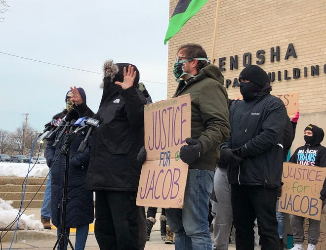 Justin Blake, the uncle of Jacob Blake, holds up seven fingers to represent the seven shots that Kenosha police officer Rusten Sheskey fired at Blake in August. The Blake family and the community group Leaders of Kenosha called on Monday for Sheskey to be fired following news the district attorney would not criminally charge him.