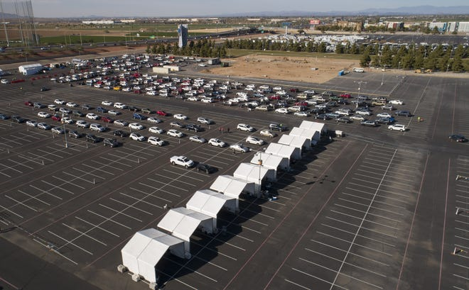 Cars line up at Arizona's first 24/7 COVID-19 vaccination site at State Farm Stadium in Glendale on Jan. 12, 2021.