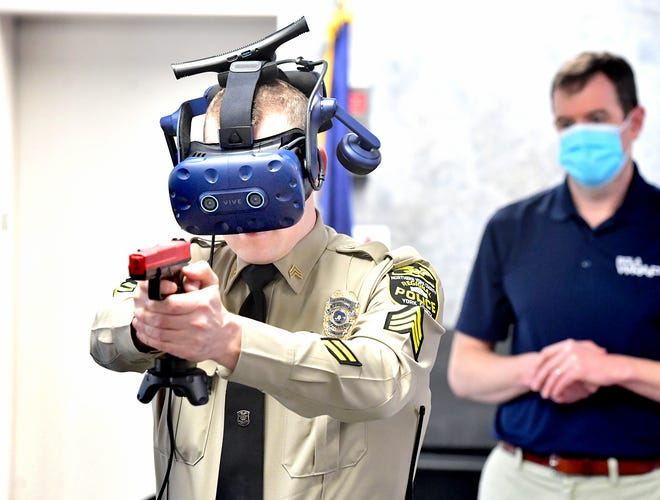 Northern York County Regional Police Department Sgt. Cody Becker, left, is watched by Ethan Moeller, vice president of WRAP Reality, while Becker used a virtual reality law enforcement simulator during training at the department Monday, Jan. 11, 2021. Bill Kalina photo