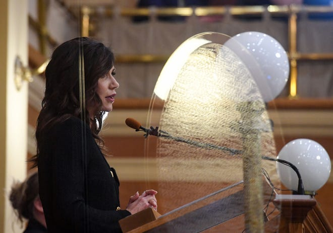 Light from the chamber entrance door reflects off plexiglass in front of Governor Kristi Noem as she gives the State of the State address on Tuesday, January 12, in the House of Representatives at the South Dakota State Capitol in Pierre.