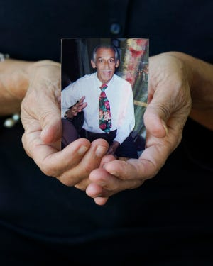 A photo of Thomas Botelho, who died from COVID-19 in early August, rests in the hands of his daughter, Alicia Borregard, on Sunday, Jan. 10, 2021, in Port St. Lucie.