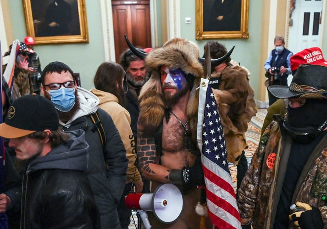 In this file photo taken on Jan. 06, 2021, supporters of President Donald Trump, including Jake Angeli (C), a QAnon supporter, enter the Capitol in Washington, D.C.