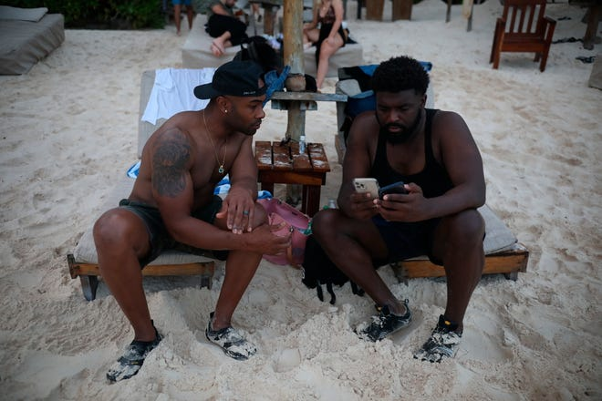 U.S. tourists Latron Evans, left, and Gearald Green, check their phones at a beach in Tulum, Quintana Roo state, Mexico, Monday, Jan. 4, 2021. The friends from Jackson, Mississippi, relaxed on lounge chairs and romped in the Caribbean waters, grateful for a break from the new coronavirus pandemic winter in the United States.