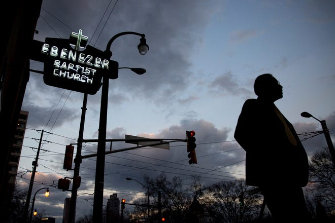 In this early Monday, Jan. 16, 2017 file photo, a man walks past the Ebenezer Baptist Church in Atlanta. The historic congregation at the heart of Atlanta, where the Rev. Martin Luther King Jr. had preached, sits at the intersection of national politics and the fate of a handful of pressing national policy fights.
