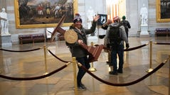 Adam Johnson, 36, of Parrish, Fla., carries the lectern of U.S. Speaker of the House Nancy Pelosi through the Roturnda of the U.S. Capitol Building after a pro-Trump mob stormed the building on Jan. 6, 2021 in Washington, DC. Johnson was arrested in Florida on Jan. 8, 2021 for his role in the U.S. Capitol riots.