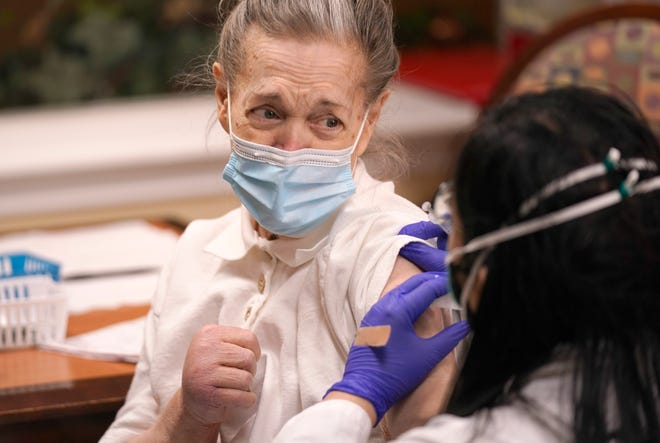 Judith Ridlen prepares to receive a COVID-19 vaccination shot on Monday at a senior living facility in Plano, Texas. The U.S. is entering the second month of the biggest vaccination effort in history with a major expansion of the campaign. (AP Photo/LM Otero)