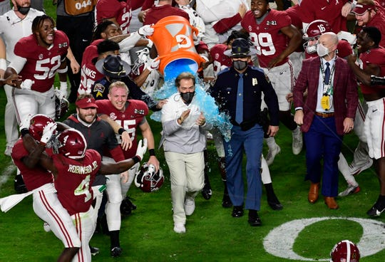 Alabama Crimson Tide head coach Nick Saban dives with Gatorade after defeating Ohio state basketball players in the College's 2021 National College Championship.