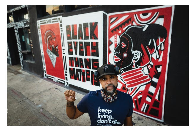 """Jonathan """"Chaka"""" Mahone stands in front of a mural he painted for a Black Everythang Matters showcase at Empire Garage."""