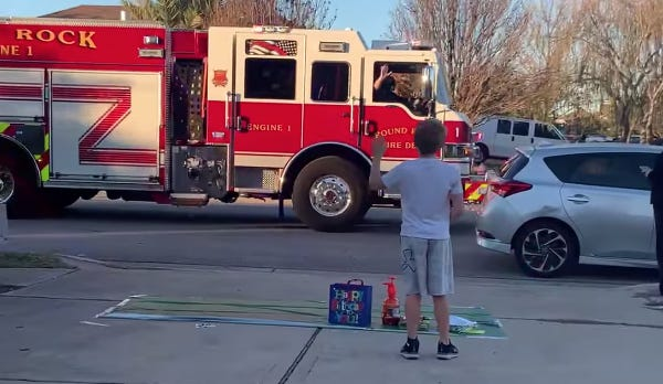 Axel Myers, 9, waves as a Round Rock fire truck drives past his home on Jan. 3 during his birthday celebration. Plans for  his birthday celebration changed when his parents contracted COVID-19.