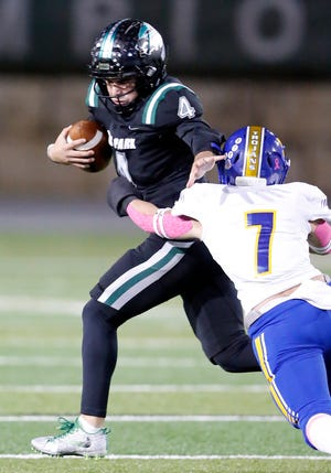 Cedar Park quarterback Ryder Hernandez, rushing against Anderson in a regular-season game, has thrown 114 touchdown passes in his career with the Timberwolves. Next year he will play baseball at Texas State.
