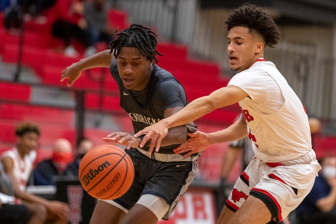 Hendrickson guard Keshawn Williams, left, and Manor guard Tyrone Haywood battle for the ball during a District 18-5A basketball game at Manor High School on Tuesday. Hendrickson won 66-62 in a battle between the top two teams in the American-Statesman's Class 5A poll.