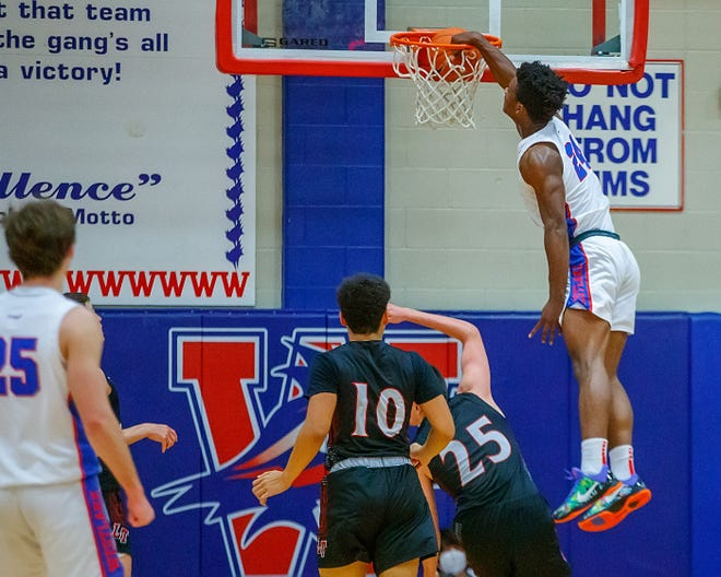 Westlake's KJ Adams dunks the ball against the Lake Travis Cavaliers during the fourth period at the District 26-6A boys basketball game Jan. 12 at Westlake High School. Despite foul trouble for Adams, the Kansas signee helped the Chaps beat Lake Travis in a battle for first place in the district race.