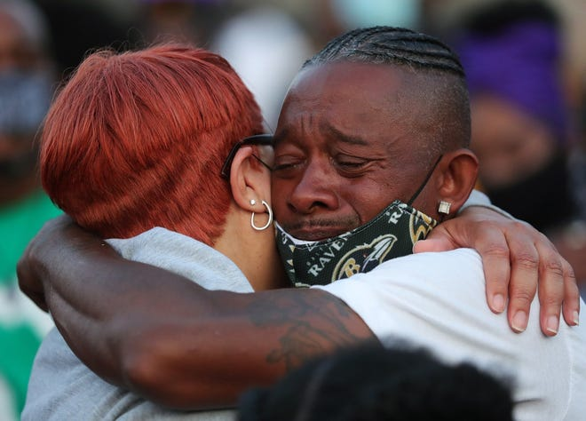 Loved ones comfort each other before a candlelight vigil in honor of Na'Kia Crawford on June 15. She's one of many people killed in Akron in a record year for violence.
