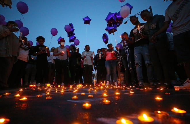 Friends and family of Na'Kia Crawford gather for a candlelight vigil June 15 on West North Street in Akron.