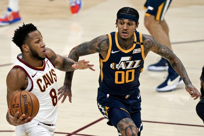 Cavaliers' Lamar Stevens (8) drives to the basket against Utah Jazz's Jordan Clarkson (00) in the second half of an NBA basketball game, Tuesday, Jan. 12, 2021, in Cleveland. [Tony Dejak/Associated Press]