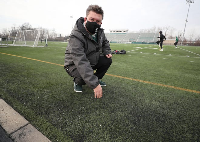 Rob Eckenrode, athletic director at Nordonia High School shows how the turf, that had a use expectancy of 8 years, has worn thin after years of use at the William Boliantz stadium. The school district is asking for donations to replace the turf which is 11 years old.